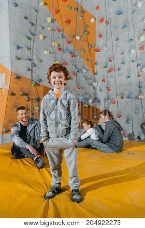 Smiling little boy in sportive attire standing in front of a climbing wall and looking at camera