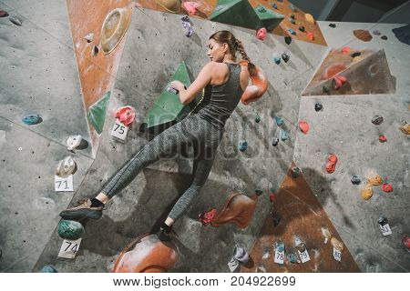 Woman Climbing Wall With Grips