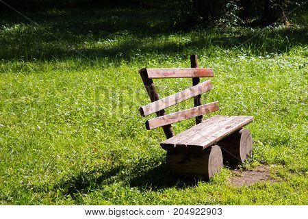 Empty Old Wooden Bench On A Green Lawn. Sunny Day, Garden Or Park, Outdoors