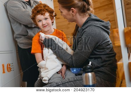 Young boy sitting on bench in locker room with his mom wiping him with towel