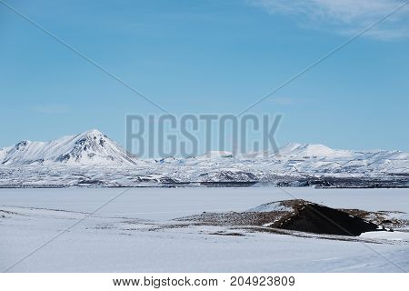 Landscape snow field with frozen lake and mountain with blue sky in winter
