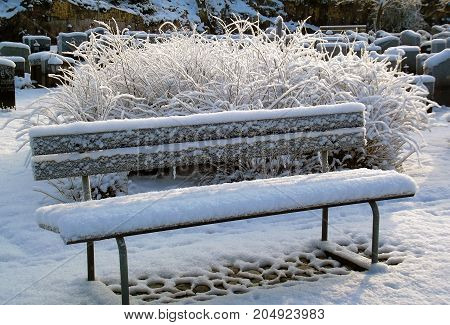 Snow covered bench in the cemetery in winter.