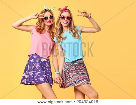 Young Woman Having Fun. Fashion. Hipster in Stylish Outfit. Sisters Best Friends Twins Crazy. Happy Pretty Girl in fashion Stylish Summer sunglasses, Trendy Hairstyle. Playful Cool Model Smiling