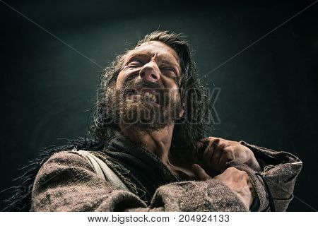 Portrait of a brutal bald-headed viking in a battle mail posing against a black background. Early medieval period.