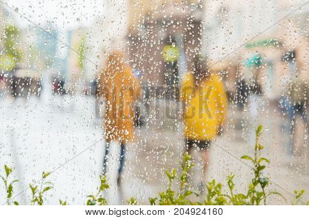 Rainy day in city. People seen through raindrops of window. Selective focus on raindrops. Silhouettes of two girls in bright beautiful yellow coats