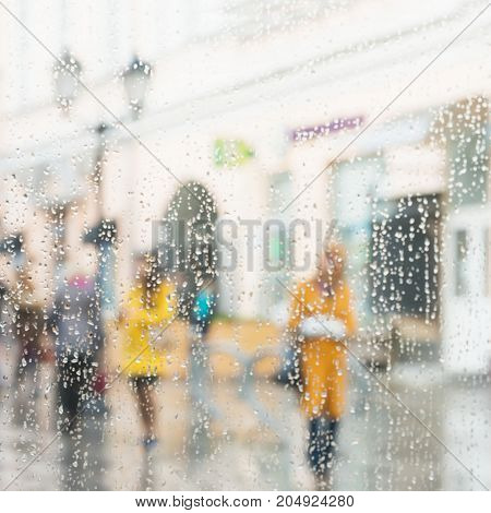 Rainy day in city. People seen through raindrops on glass. Selective focus on the raindrops. Silhouettes of girls in bright beautiful yellow coats
