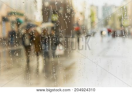 Rainy day in city. People with umbrella seen through raindrops on glass of window . Selective focus on the raindrops. Concept of modern city, love, lifestyle. Abstract blurred background poster