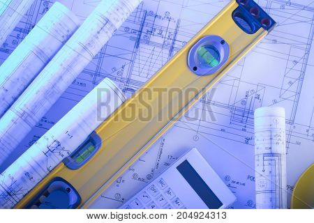 Architecture concept. Rolls with blueprints and carpenter's level.