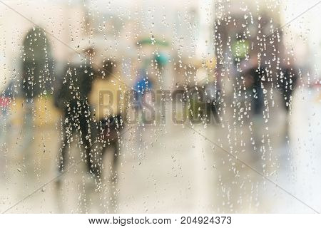 Abstract blurred silhouettes of people with umbrellas on rainy day in city, two persons seen through raindrops on window glass, blurred background. Concept of seasons, weather