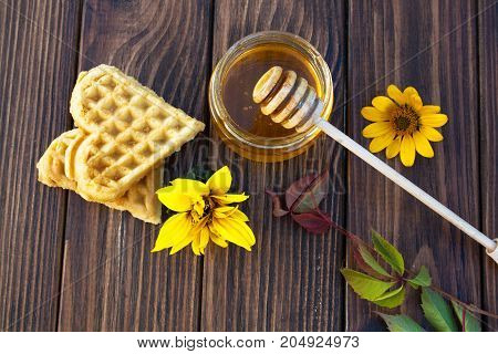 Honey sweet waffles in the shape of heart and sunflower on a wooden background. View from above