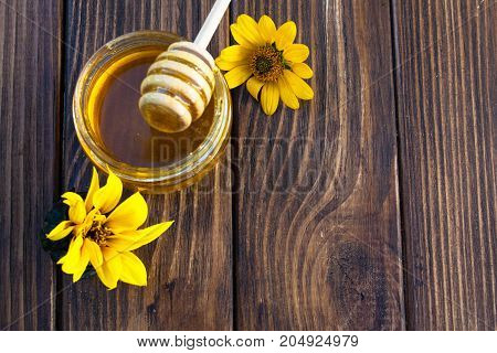 sweet honey and sunflower flowers on a wooden background