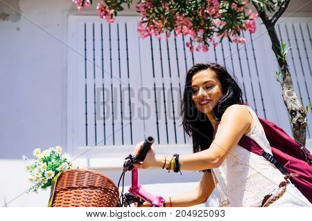 Beautiful young woman riding bicycle with flowers in basket, enjoying summer time.