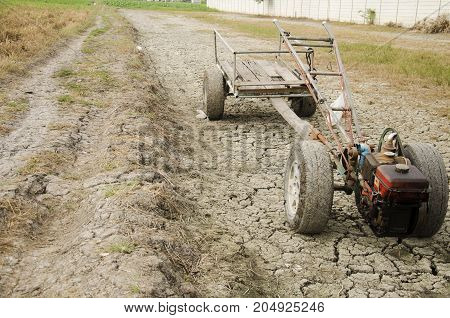 Damage Old Tractor And Trailer Towing Stop On Paddy Field Wait Spring Season On Desert Land