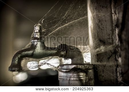 A tap covered with spider web no more water.