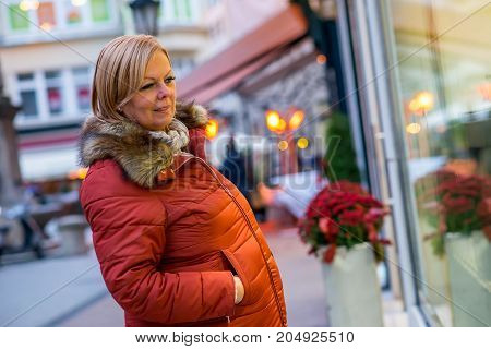 A nice middle age woman standing and looking at the window of a shop in a winter jacket