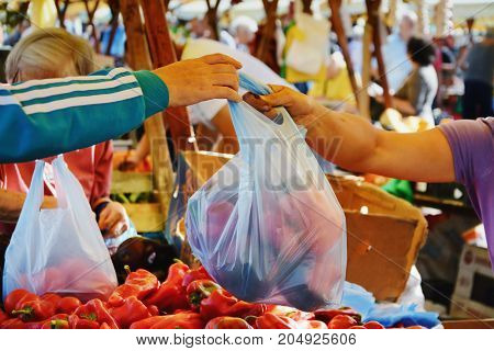 Man shopping vegetables at the market. Farmer vendor hands over plastic bag filled with fresh vegetables to a buyer