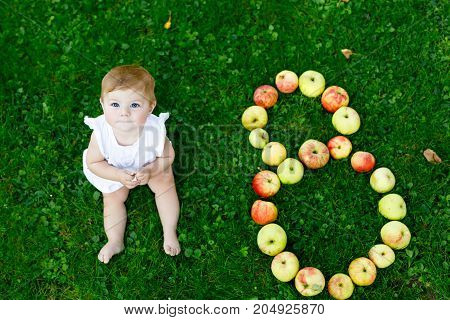 Cute baby girl with number 8 as eight months made with ripe apples on a farm in early autumn. Little baby girl playing in apple tree orchard. Kids pick fruit in a basket. Healthy nutrition.