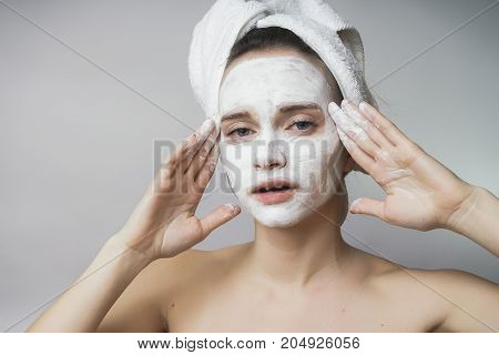 Woman with white cosmetics mack on face, scrub,hydrating
