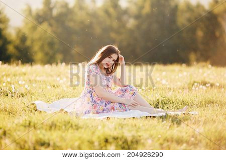 pregnant girl in a light dress sits on a plaid in the park. Concept maternity, pregnancy, childbirth, a healthy walk in the park, nature help. Sunset