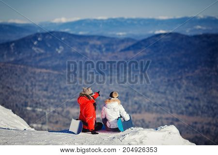 Friends of a snowboard girl are sitting on the snow with snowboards and looking into the distance.