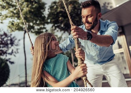 Dad With Daughter On Swing