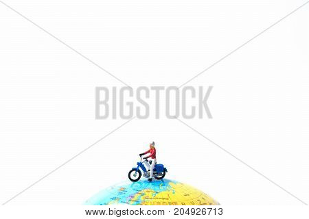 Tiny miniature model of the man is riding the motorbike or motorcycle on globe using as travelling journey travel to destination background concept.