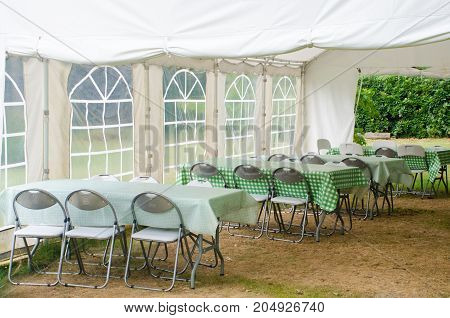 Green Chairs under outdoor Marquee in field