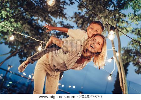 Attractive young woman with her little cute son are spending time together in park in the evening. Mom and son are having fun and smiling outdoors on a terrace with garland of light bulbs.