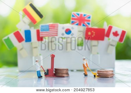 Workers are transferring or loading coins with international flags background using as teamwork money transfer and partnership business concept.