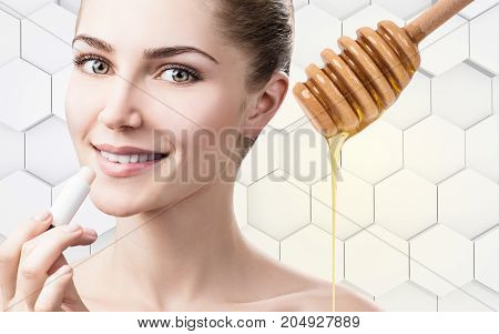 Young woman putting organic lipbalm with honey on lips over gray honeycombs background.