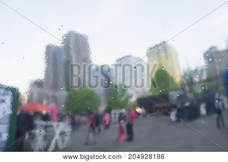 Rainy day in city. Distorted reflection of city and people on metal surface, reminiscent of art, watercolor, impressionism. Concept of modern city, lifestyle. Abstract blurred background