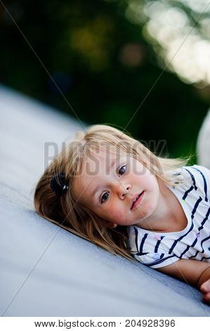 Portrait of a two year old girl in a striped dress. Nice face short blond hair serious look. Cute baby lies on the ground and looks curiously at the camera.