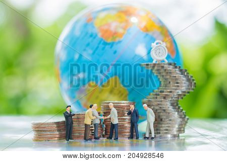 Miniature businessman handshaking with globe and growing stacks of coins background using as commitment agreement investment and partnership business concept.