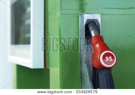 Fuel nozzle dispensing pump with octane number of petrol 95 at old gas station close up