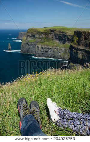 Cliffs of Moher, North Ireland sea coastline, sunny summer landscape, feet of resting people