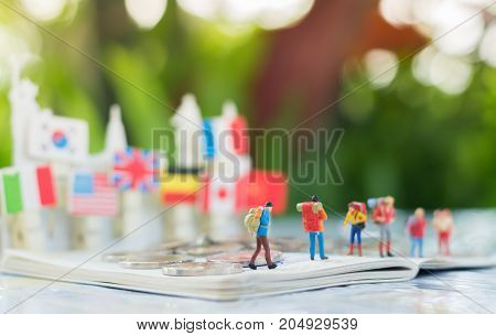 Tiny miniature model of travelers or backpackers are standing on a passport and a pile of coin with international flag background using as traveling journey travel to destination background concept.