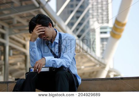 Frustrated stressed Asian businessman with hand on forehead sitting on staircase in the city. Depressed unemployment business concept.