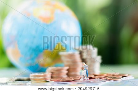 Miniature shoppers with shopping cart figure on a credit card or debit card with stack of coins and globe background using as shopping e-commerce and online business concept.