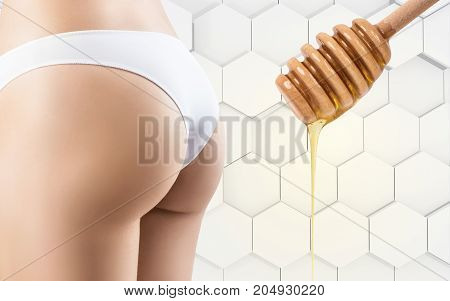 Honey flows down on woman buttocks. Massage concept. Hair removal concept.