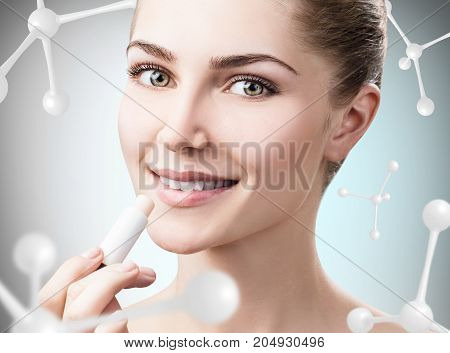 Beautiful young woman putting lipbalm among molecules over gray background. Innovation cosmetics concept.