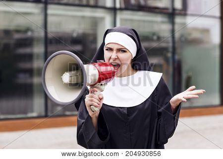 Young sister nun speak to megaphone outdoors in the city.