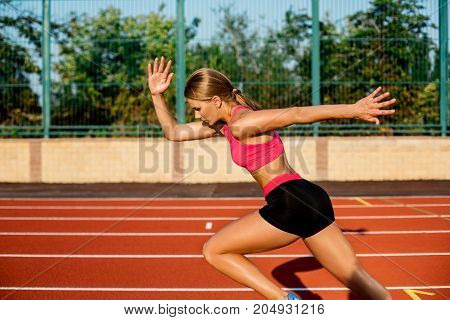 Side view beautiful young woman exercise jogging and running on athletic track on stadium. Sport, healthy lifestyle concept.