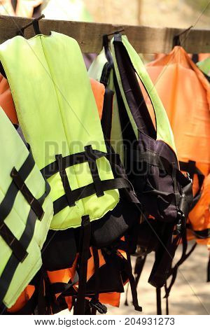 Colorful Life jackets hanging on the row.