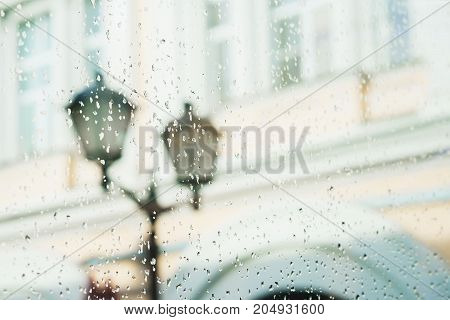 Close-up of a street lamp. View from the window with rain drops on city street, blurred street bokeh. Concept of autumn weather, seasons, modern city.