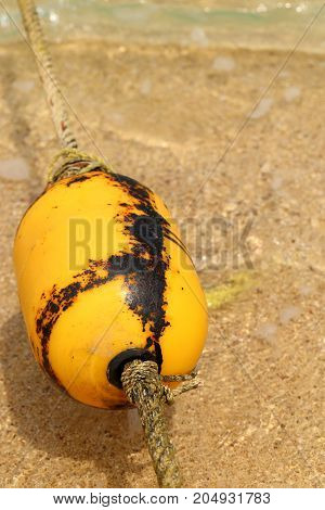 Yellow buoy rope on sea beach close up.