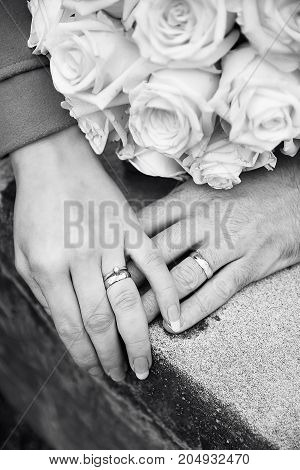 Bride and groom hands with rings and flowers b/w