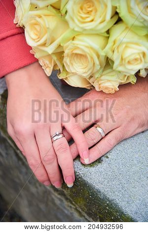 Bride and groom hands with rings and flowers