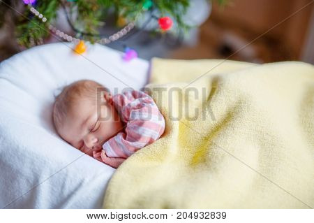 One week old newborn baby sleeping near Christmas tree with colorful garland lights on background. Closeup of cute child, little baby girl dreaming peaceful. Family, Xmas, birth, new life