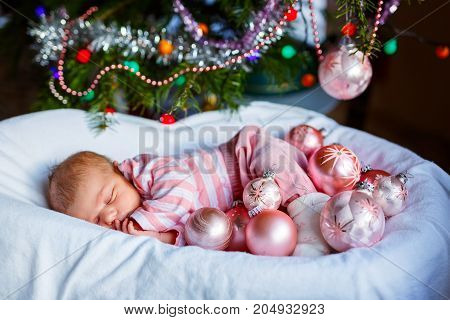 One week old newborn baby with pink balls near Christmas tree with colorful garland lights on background. Closeup of cute child, little baby girl looking at the camera. Family, Xmas, birth, new life