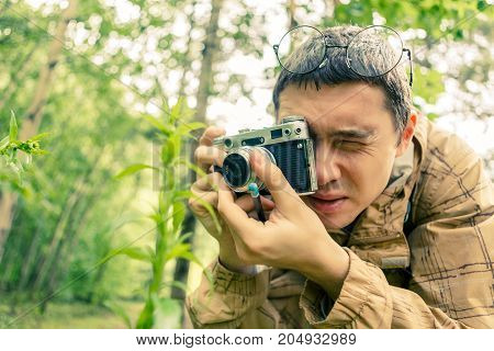 Picture of brunet with camera in woods among plants and trees